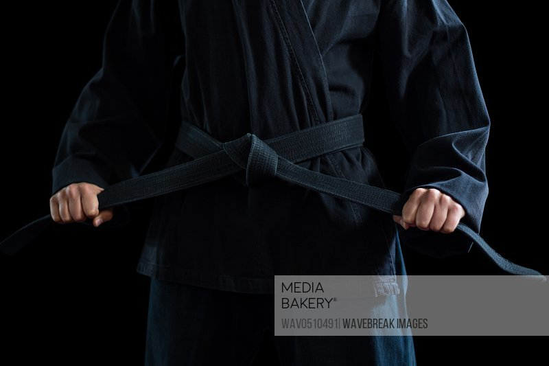 Mid section of confident karate player holding his belt against black background