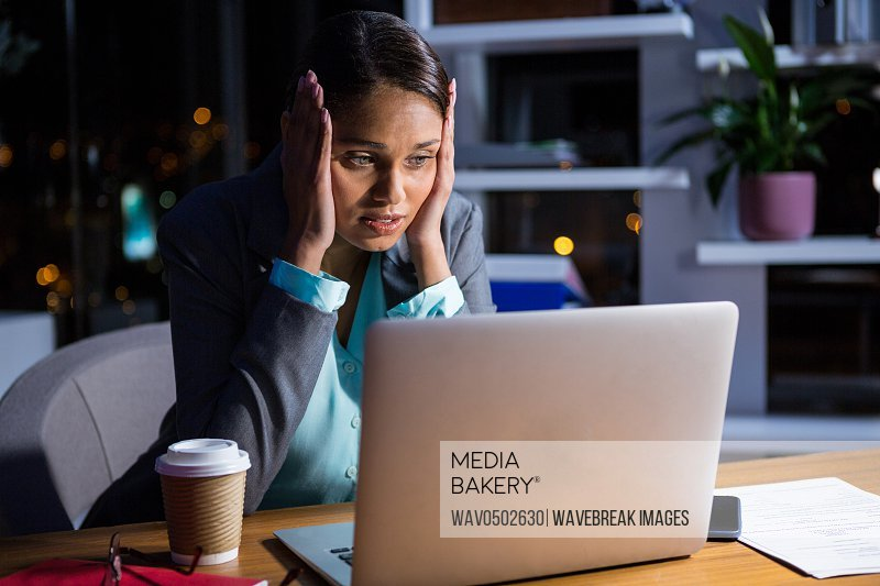 Thoughtful businesswoman working on laptop in office at night
