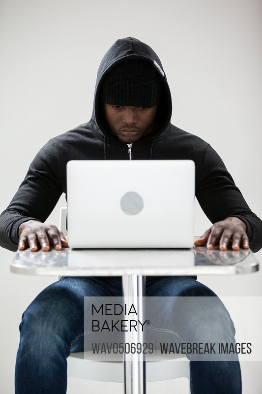 Hacker sitting at table and using a laptop against white background