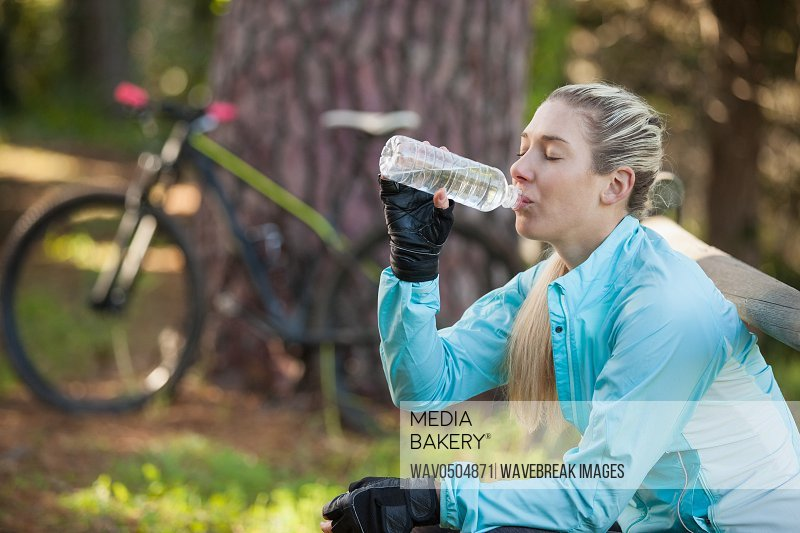 Female mountain biker drinking water in the forest