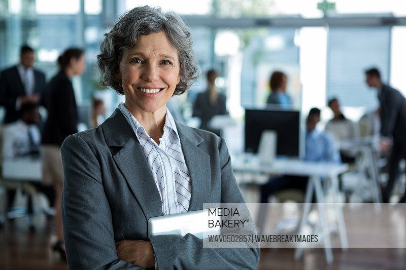 Portrait of smiling businesswoman standing with arms crossed in office