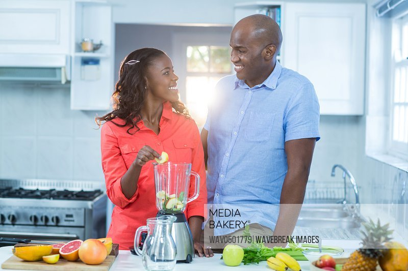 Couple smiling and looking at each other in kitchen