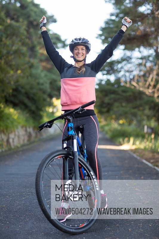 Excited female biker standing with mountain bike on the country side road
