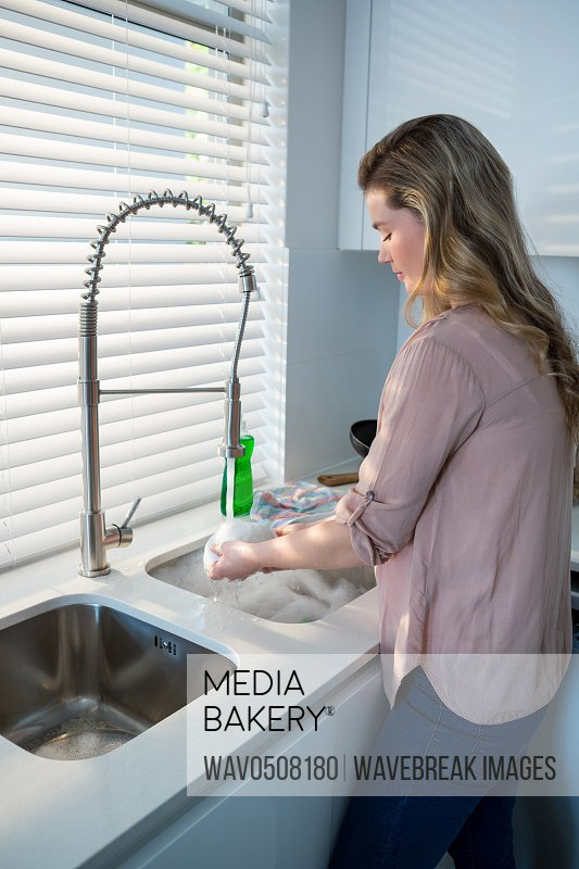 Woman washing bowl under sink in kitchen at home
