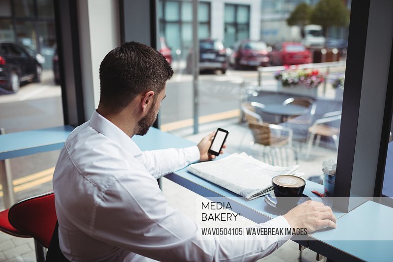 Man using mobile phone while having coffee in office