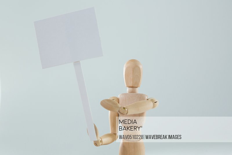 Wooden figurine holding blank sign board against white background