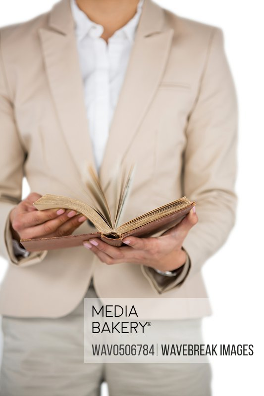 Mid section of Businesswoman flips through the pages of a book on white background