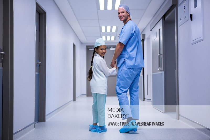 Portrait of doctor and girl walking in corridor at hospital
