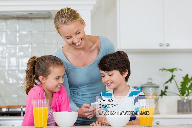 Mother showing mobile phone to kids while having breakfast