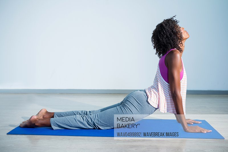 Woman doing cobra pose on exercise mat in gym