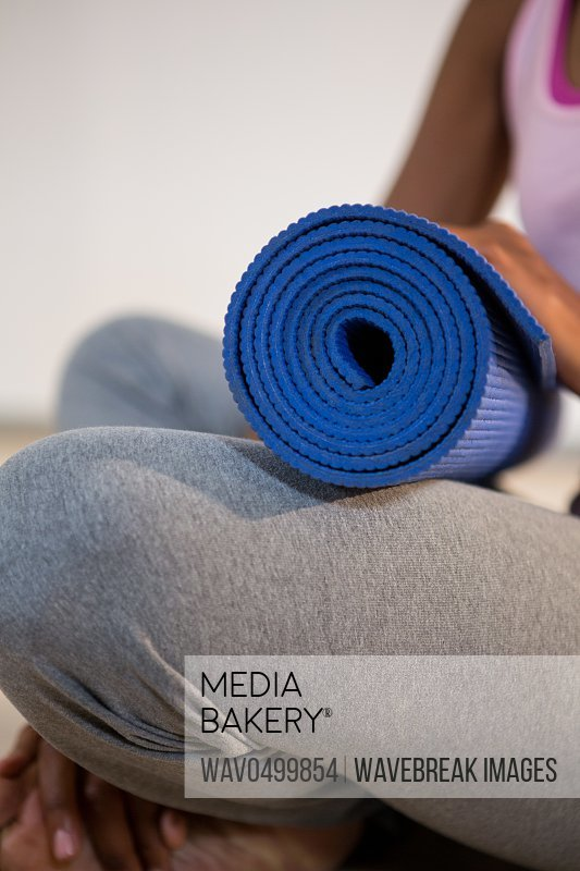 Close-up of woman holding exercise mat in gym
