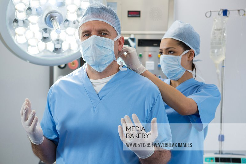 Surgeon helping in tying surgical mask to her co-worker in operation room