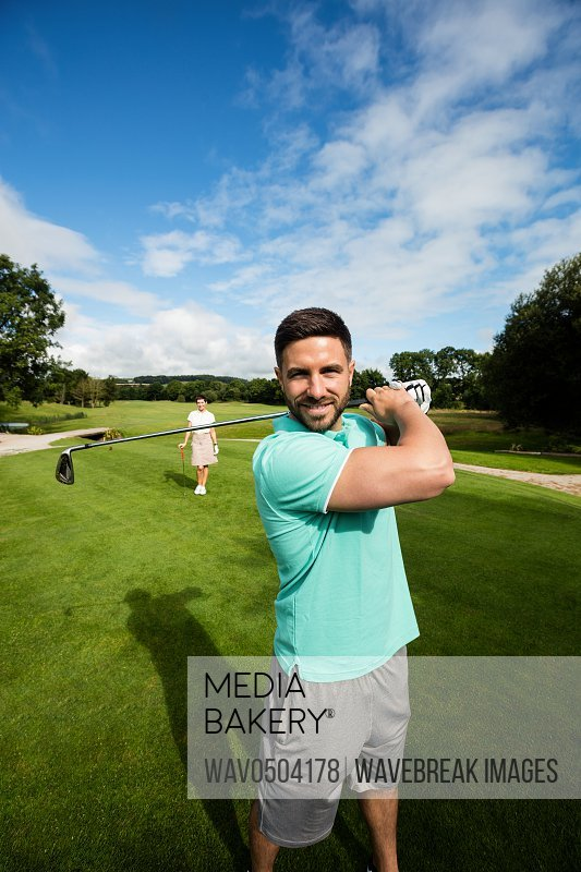 Portrait of smiling man standing with golf club and bag in golf course