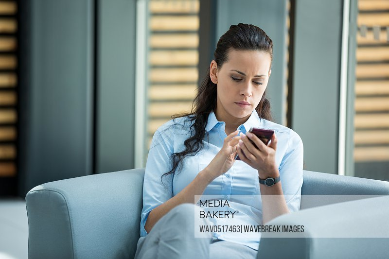 Businesswoman sitting and using a mobile phone