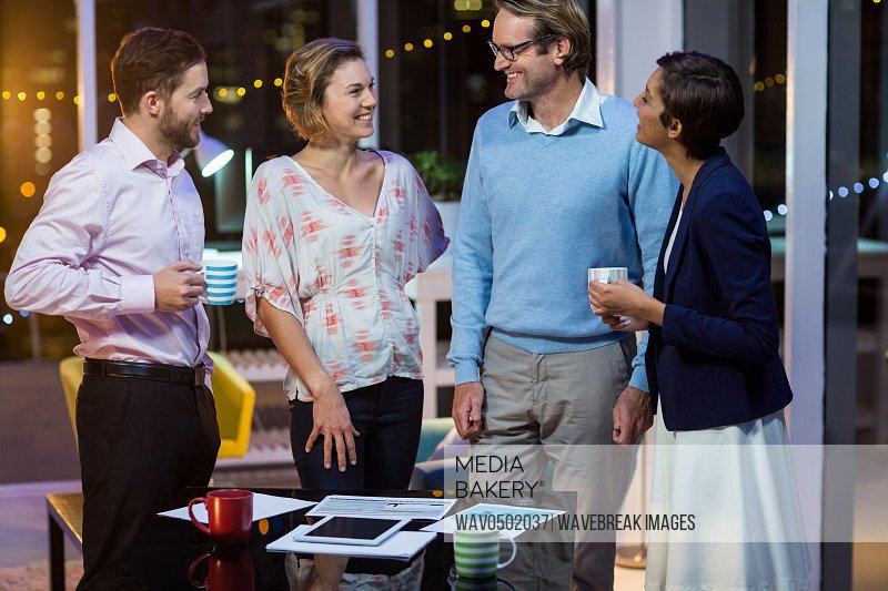 Businesspeople interacting with each other while having coffee in office