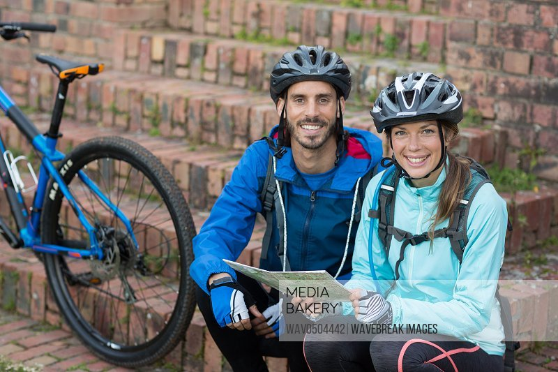 Portrait of biker couple with a map in countryside
