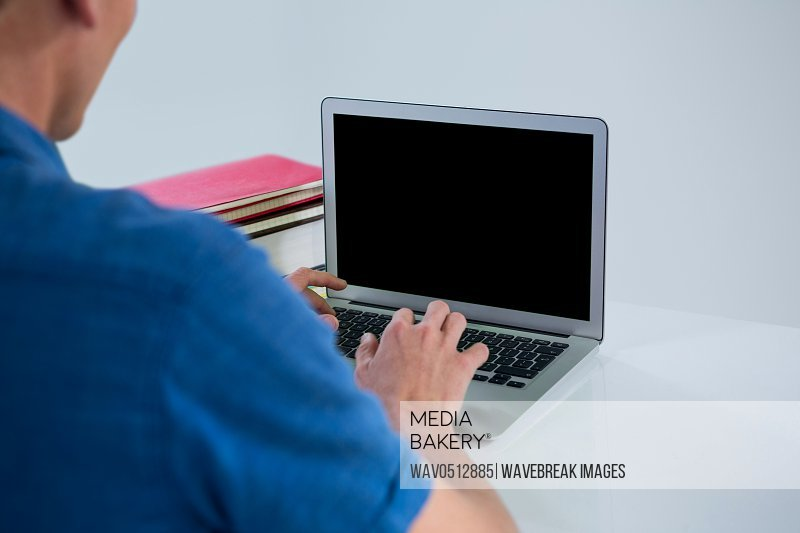 Rear view of man using laptop in office