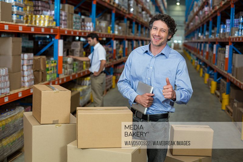 Portrait of smiling warehouse staff showing his thumbs up in the warehouse