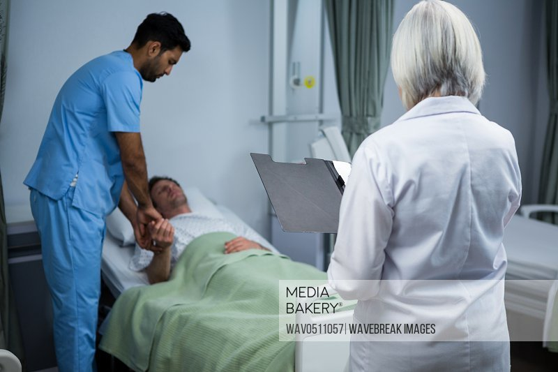 Doctor and surgeon consulting patient in ward of hospital
