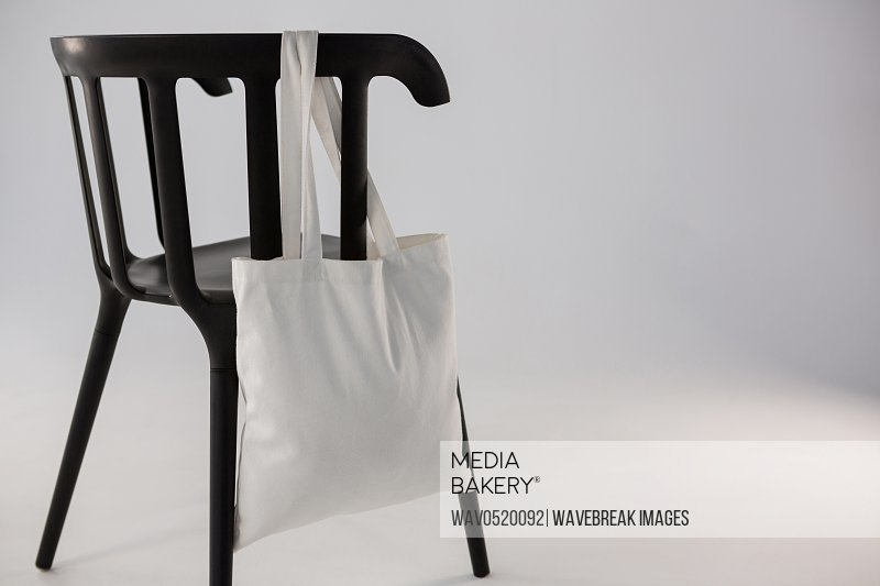 White bag hanging on a black chair