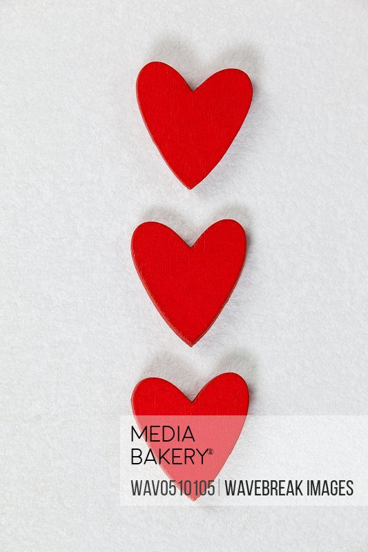 Close-up of three red hearts kept in a row on white background