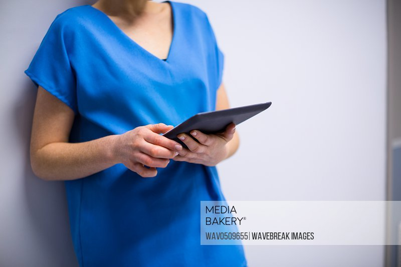 Mid-section of doctor using digital tablet in hospital