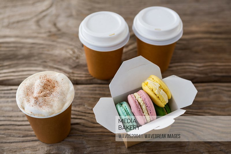 Macaroons with coffee on wooden table