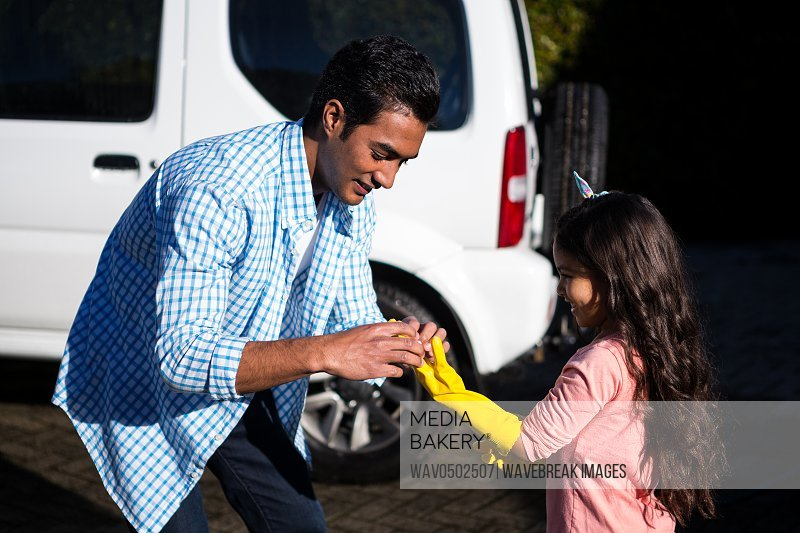 Father helping daughter to wear gloves outside house