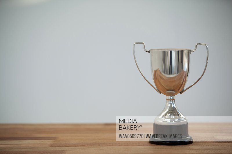 Close-up of champion silver trophy on wooden table