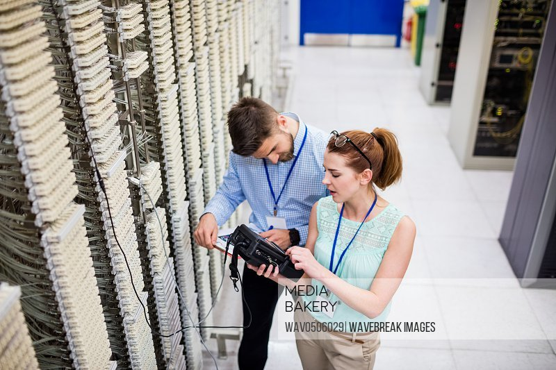 Technicians using digital cable analyzer in server room