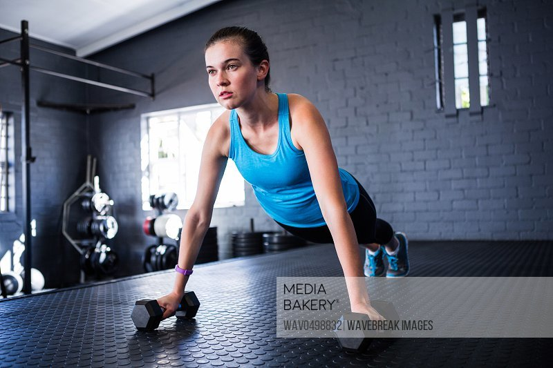 Sporty young woman doing push-ups with dumbbells in gym