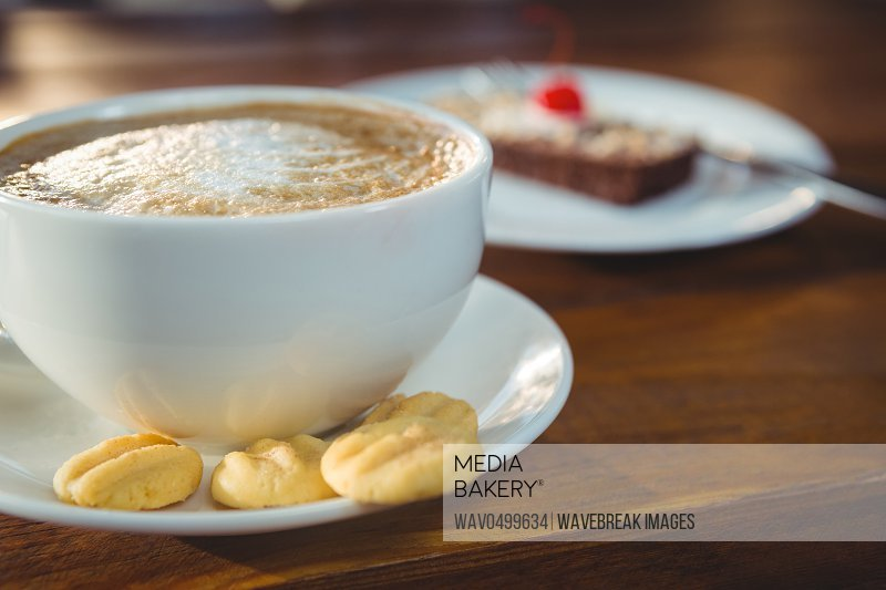 Close-up cappuccino with cookies on table in cafeteria