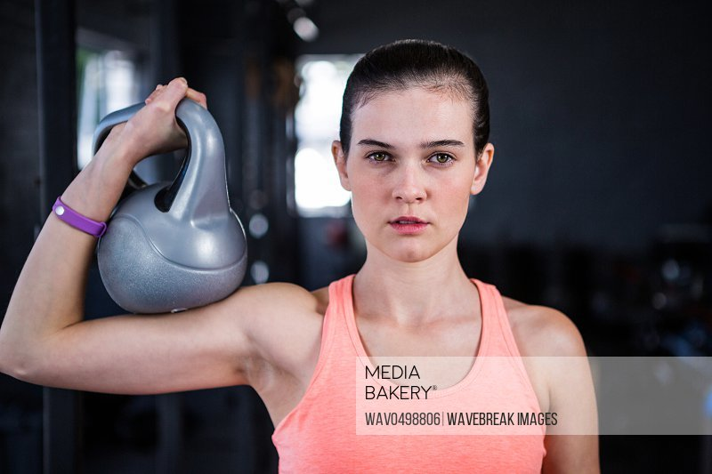Portrait of serious female athlete holding kettlebell while standing in gym