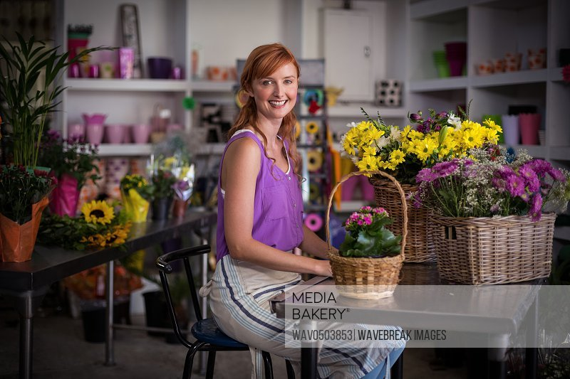 Female florist sitting with basket of flowers in the shop