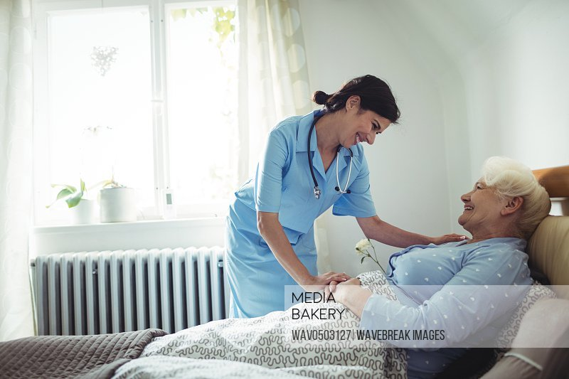 Nurse interacting with senior woman on bed at bedroom
