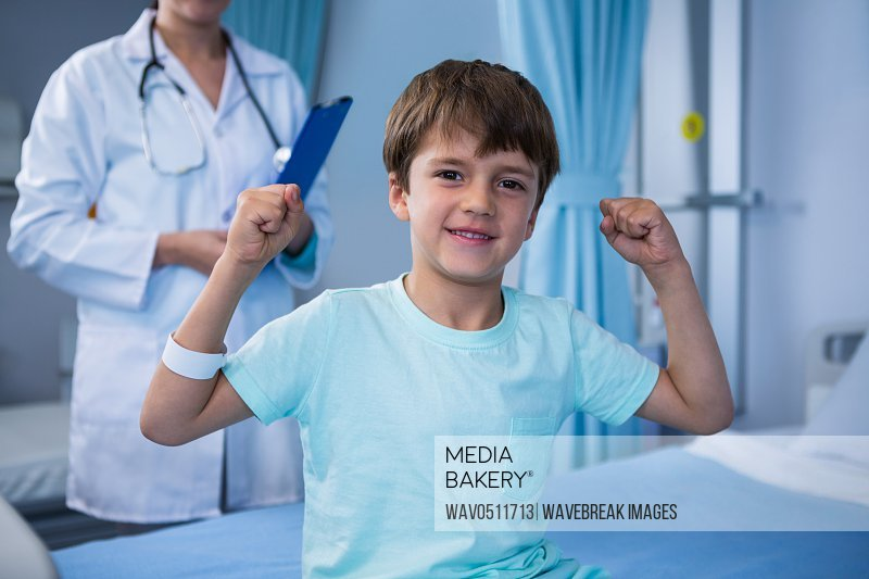 Portrait of boy flexing his muscles and female doctor standing in background in ward