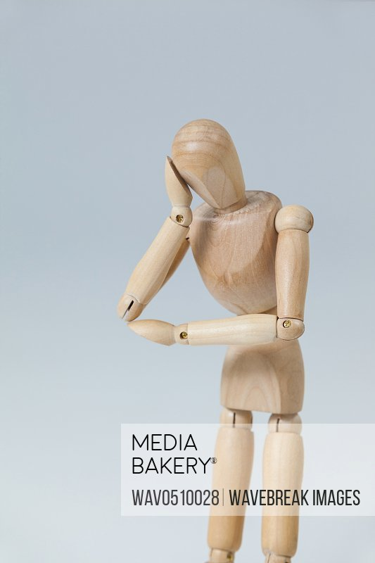 Thoughtful wooden figurine pretending to lean against white background