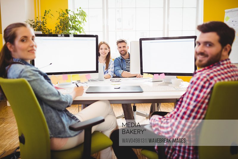 Portrait of smiling graphic designers sitting at desk in creative office