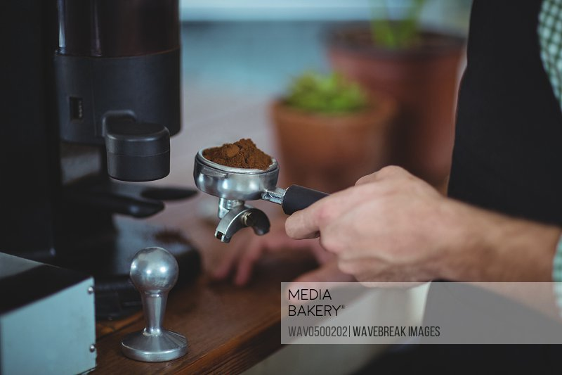 Waiter holding portafilter filled with ground coffee in cafe