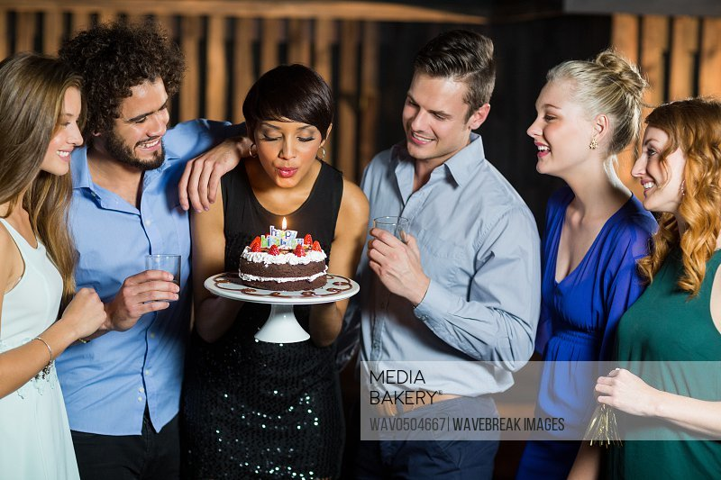 Woman blowing the candle on her birthday cake with her friends in bar