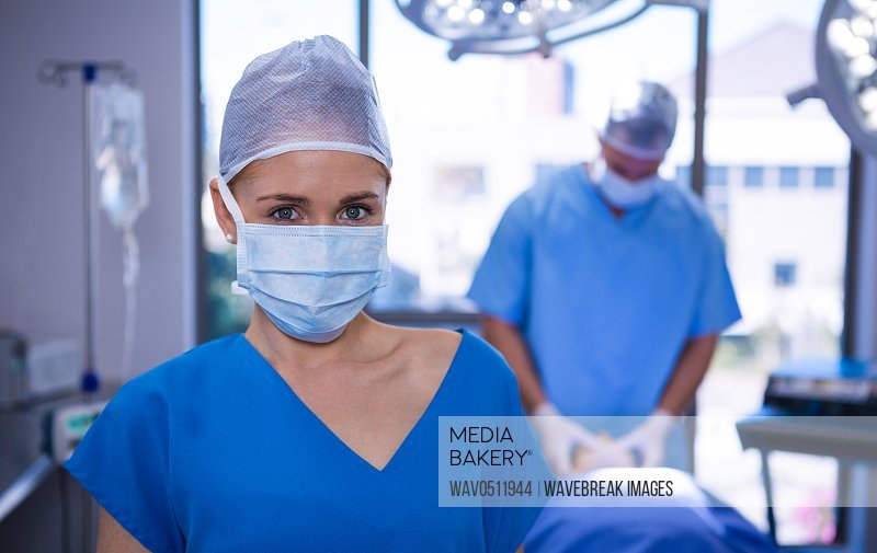 Portrait of female nurse wearing surgical mask in operation theater at hospital