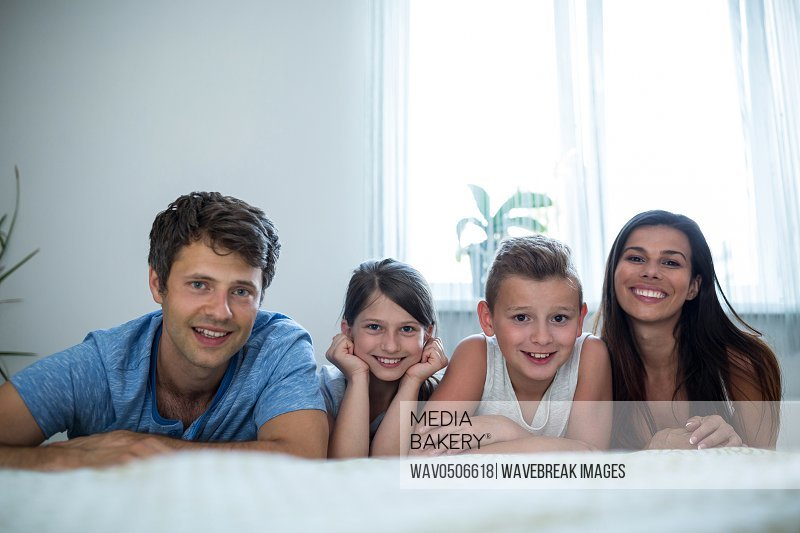 Portrait of parents and kids lying in bedroom at home