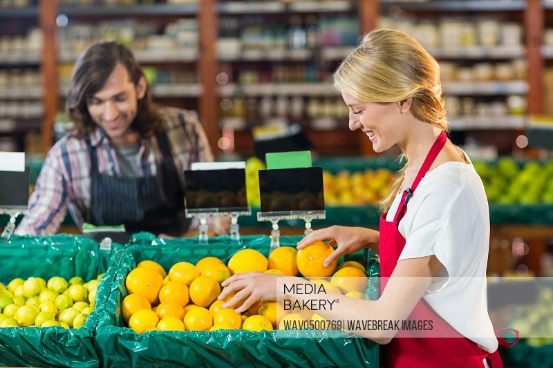 Smiling female staffs checking fruits in organic section of supermarket