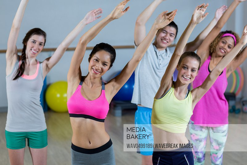Portrait of group of fitness team posing with arms up in fitness studio
