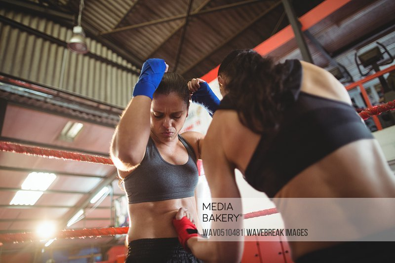 Two female boxers fighting in boxing ring at arena