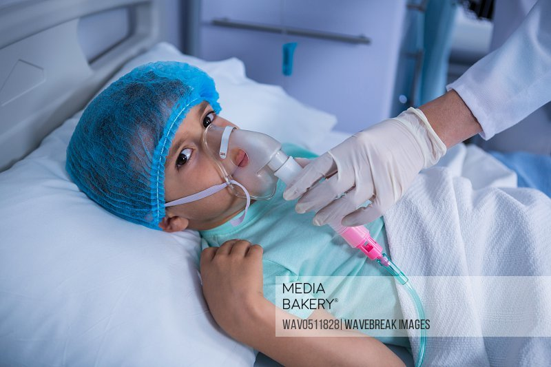 Doctor placing an oxygen mask on patient in ward at hospital