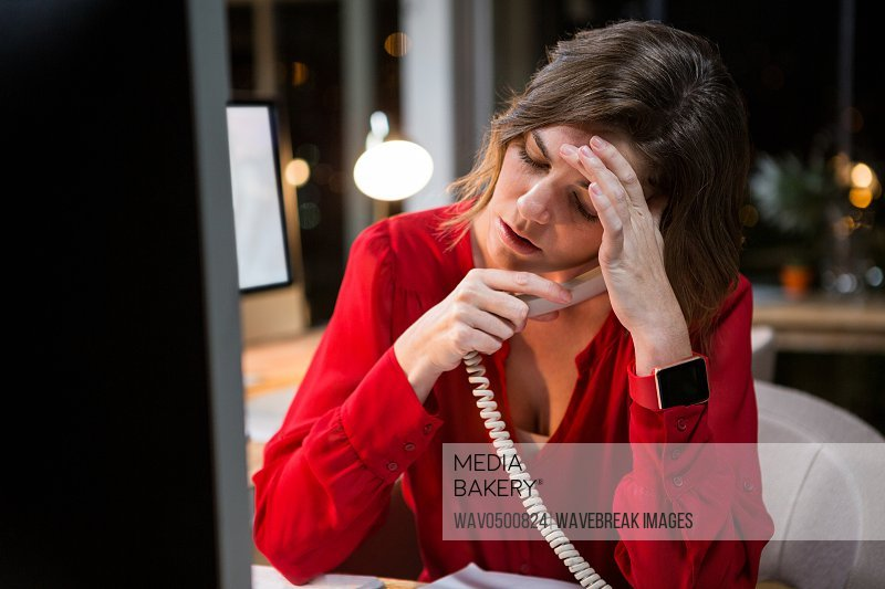 Stressed businesswoman talking on phone while working on computer at her desk in the office