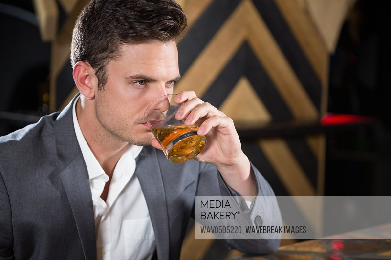 Depressed man having glass of whisky at counter in bar