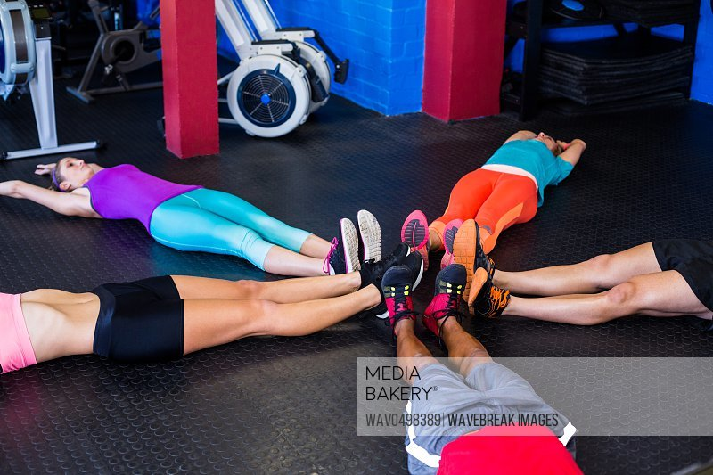 People stretching while lying in gym