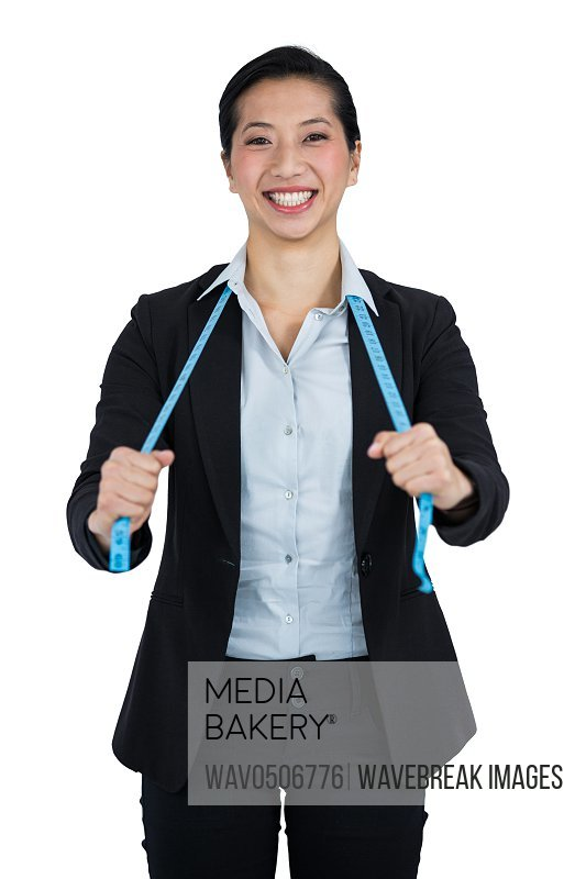 Portrait of businesswoman holding a measuring tape against white background